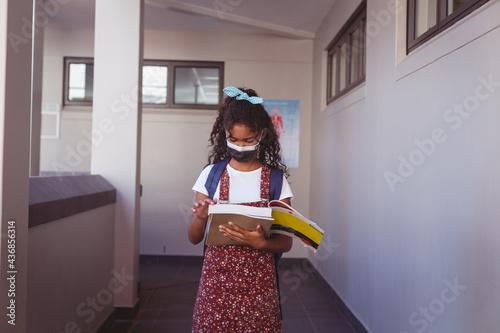African american schoolgirl in face mask standing in school corridor reading book