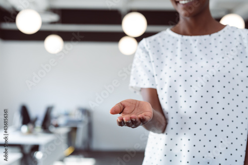 Midsection of smiling african american businesswoman with open hand