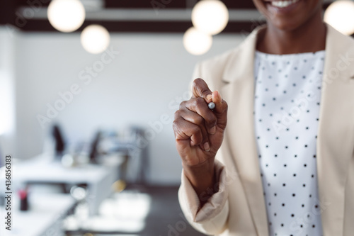 Close up of hand of african american businesswoman writing on interactive screen