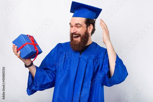 Fotografia Amazed student man in blue bachelor holding gift box
