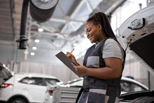 Afro American Woman Mechanic Writing On Clipboard At Repair Garage, Wearing Uniform Overalls. Young Mechanic Engineer Female Taking Notes On Clipboard For Examining A Vehicle
