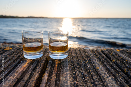 Fototapeta Drinking single malt Scotch whisky at sunset with sea, ocean or river view, priv