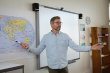 Caucasian Male Teacher Teaching Geography To Students In The Class At Elementary School
