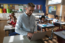 Caucasian Male Teacher Using Laptop While Sitting In The Class At Elementary School