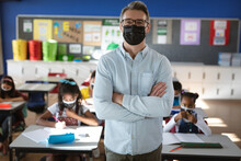 Portrait Of Caucasian Male Teacher Wearing Face Mask Standing In The Class At Elementary School