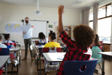 Rear View Of African American Boy Raising His Hand While Sitting On His Desk At Elementary School
