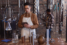 Caucasian Male Worker Wearing Apron Using Digital Tablet At Gin Distillery