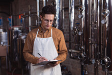 Caucasian Male Worker Wearing Apron Writing On Clipboard At Gin Distillery