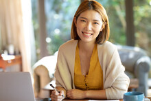 Portrait Of Smiling Asian Woman Working From Home