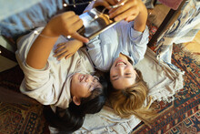 Smiling Asian Woman With Her Daughter Using Tablet Taking Selfie Lying Under Blanket Tent