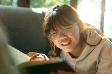 Smiling Asian Girl In Glasses Reading A Book And Lying On Sofa