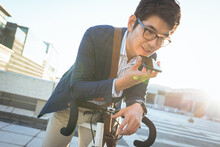 Midsection Of Asian Businessman Talking On Smartphone Leaning On Bike In City Street