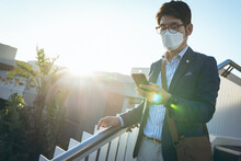 Asian Businessman Wearing Face Mask Using Smartphone In City Street