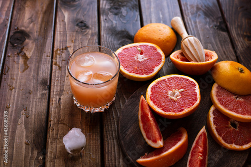 sliced pieces of grapefruit lie on the table on the dark wooden countertop Fototapet