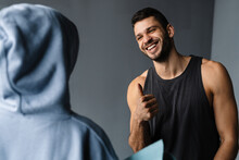 Young Fitness Coach Gesturing And Talking With Sportswoman During Class