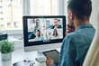 Thoughtful young woman talking to collegues by video call while sitting in office