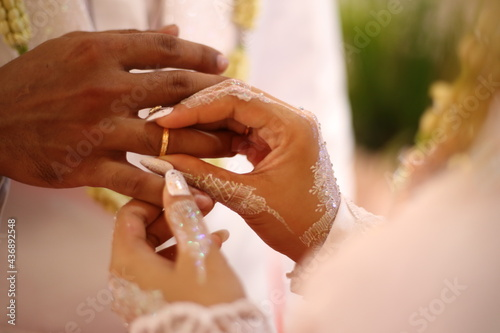 Foto bride putting ring on groom