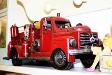 Closeup Shot Of A Red Tin Truck On A Shelf