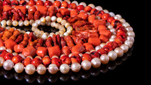 Shiny Red Coral Beads Of Different Shape And Nacreous Pearl Necklaces   Laid Out In A Circle On A Black Background. Natural Gemstone, Luxurious Isolated Jewelry. Wallpaper, Background, Texture.