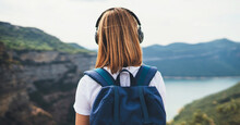 Back View Girl Tourist With Light Hair Dreams Listening To Music In Headphones Standing On Top Of Mountains, Traveler With Backpack Enjoys Walk Along Lake Valley Among Green Hills, Copy Space
