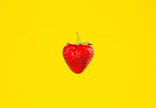 One Fresh Strawberry On A Yellow Background