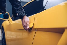 Man Is Reaching For The Car Door Handle. Car Rental Or Car Theft Concept