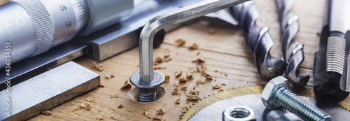 Fotografie, Obraz hex bolt screw by hex wrench in wooden oaks plate with with vernier caliper and