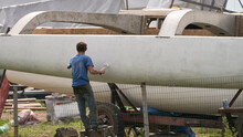 A Man Builds A Catamaran With His Own Hands After Work. He Primed The Bottom Of The Catamaran. Selective Focus.
