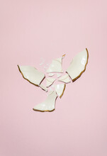 Broken Wedding Plate In Flying Bird Shape In Ivory Color With Gold Edges Against Powdery Pink Background. Minimal Artistic Flat Lay Party Concept.