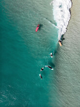 Aerial View Of Surfers Catching A Wave In Noosa, Queensland, Australia.