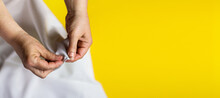 Seamstress Hands With White Cloth On Bright Trendy Color Yellow Background. Female Hands With A Needle, Thread And Thimble. Women Needlework. Top View. Minimalism Concept.