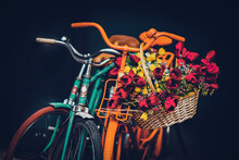 Old Multicolored Bicycles With Basket Of Spring Flowers On Dark Background, Low Key Photo