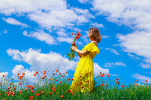 Pretty Young Woman In A Yellow Dress With A Bouquet Of Red Poppies Walks Across The Field. Happiness Concept