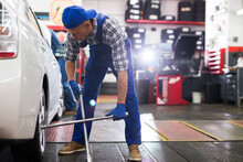 American Mechanician Changing Car Wheel And Tire Of Modern Car In Auto Repair Shop
