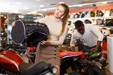 Nice Girl Looking For New Duffel Bag For Motorcycle In Shop Of Moto Equipment