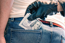 A Black-gloved Hand Pulls The Money Out Of His Back Pocket. The Concept Of Petty Crime And Theft. Bundle Of Dollars In A Jeans Rear Pocket And A Hand Pulling Them Out