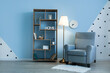 Leinwandbild Motiv Glowing lamp with armchair and book shelf near color wall