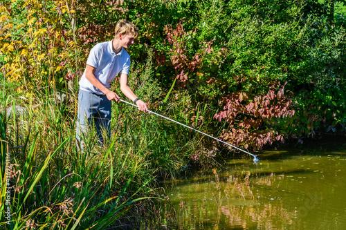 Junger Golfer fischt einen Ball aus dem Teich Fototapet