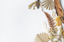 Boho Dried Flower Arrangement Of Banksias, Bark, Ruscus Leaves, Bunny Tails, Yellow Flowers And Palm Fronds, Photographed From Above, On A White Background. Earthy Tones Of Yellow, Brown And Creams.