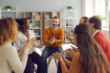 Happy Diverse People Applauding Mature Man In Group Therapy. Team Of Grateful Patients Thank Therapist For Good Psychological Help Session. Success, Positive Encouragement, Overcoming Problems Concept