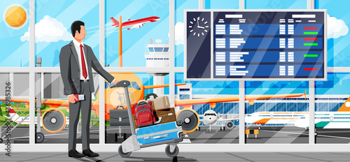 Fotografia, Obraz Man And Hand Truck Full Of Bags In Terminal Interior