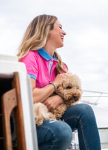 Cheerful Woman Caressing Poodle On Yacht Under Cloudy Sky