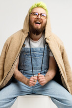 Bearded Man Wearing Fashionable Jacket And Denim Overalls, Expressing Positive Emotions, Laughing, Looking Up With Optimism, Sitting On Cube. Indoor Studio Shot Isolated Over Gray Background.