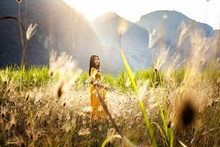 A Beautiful Woman In An Indian Dress Stands Among The Valleys, Grasslands And The Evening Sun.
