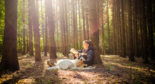 Woman With Dog Reading A Book In Forest