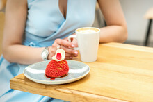 Young Female Drinking Coffee With A Piece Of Cake Sitting At The Table In A Cafe Outdoors