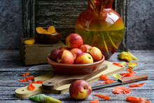 Still Life Of Juicy Peaches In A Bowl And Yellow Iris Flowers In A Vase On A Dark Wooden Background