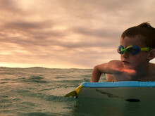 Boy On A Bodyboard In The Ocean At Sunset