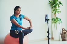 Ethnic Sportswoman Exercising On Pilates Ball Against Smartphone