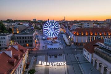 Białystok, widok z lotu ptaka o zmierzchu na Ratusz, Rynek Kościuszki, koło widokowe i napis #Białystok